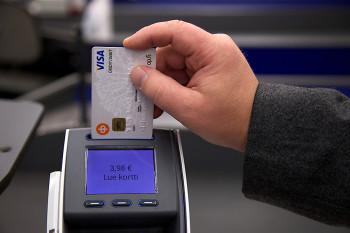 En hand som håller ett betalkort vid en kortläsare