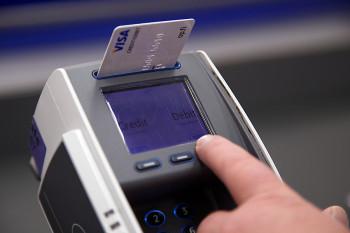 Ett finger vid en kortläsare med ett betalkort i, trycker på debit-knappen