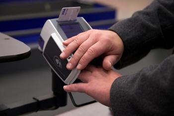 En hand som täcker över kortläsaren samtidigt som andra handen knäpper in koden